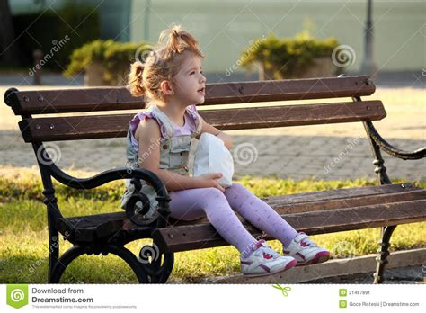 girl sitting on bench little girl sitting on the bench stock image image 21467891