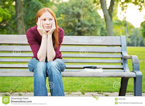 woman sitting on bench bored woman sitting on a bench stock photos image 33307283