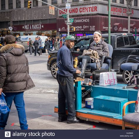 a woman gets a new a gets boots shined at a shoe shine stand on