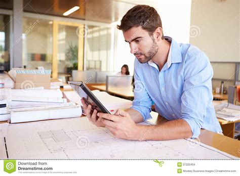 male architect with digital tablet studying plans in male architect with digital tablet studying plans in
