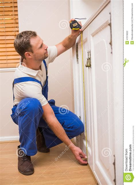 Construction Worker Using Measuring Tape Stock Photo