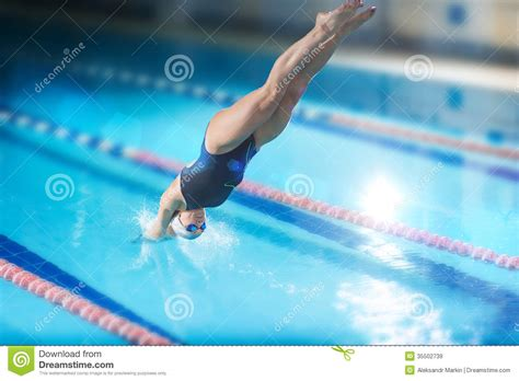 dive sport swimmer that jumping into indoor swimming pool