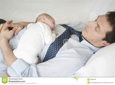 sleeping with baby in bed newborn baby sleeping with father in bed stock images