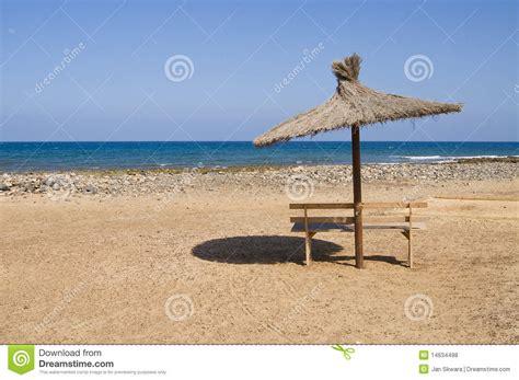 bench on the beach bench and umbrella on a beach royalty free stock photos