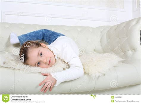 little girls sofa little happy girl in jeans lies on white leather sofa