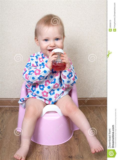 Baby Pinkis 2 Pot small baby is sitting on a pink pot and drinks water stock photos image 29056173