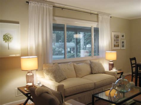 Make your picture windows look huge by hanging bamboo blinds and floor length curtains high and wide