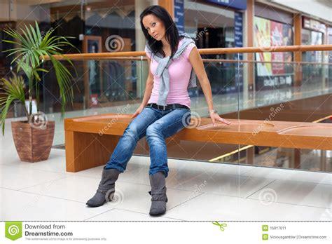 bench over posing brunette on bench over mall background stock image