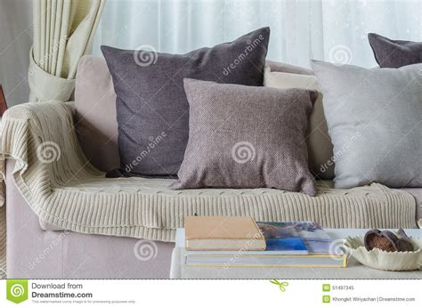 blanket on sofa pillows and blanket on earth tone sofa in living room