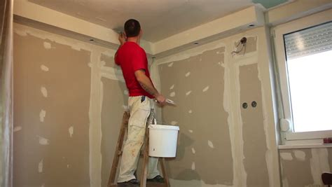 painting work man s hand plastering a wall with trowel construction