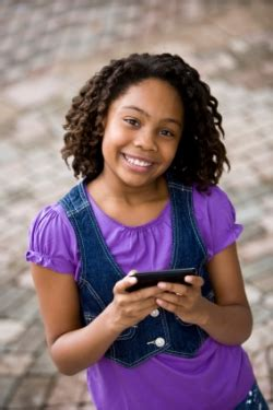 preteen black young african american girl holding cellphone sending text