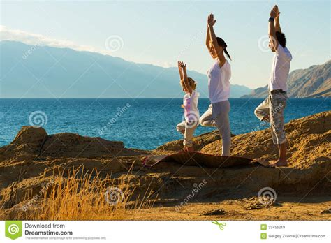 imagenes yoga en familia familia joven que hace ejercicio de la yoga en la playa