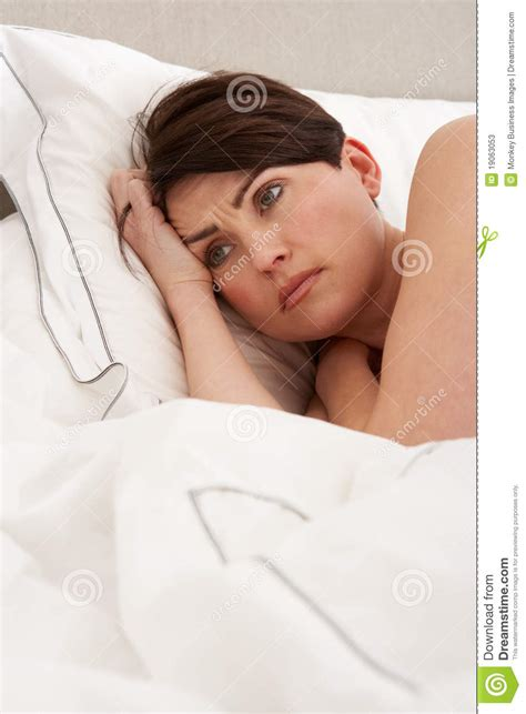 laying in bed worried woman laying awake in bed stock photos image