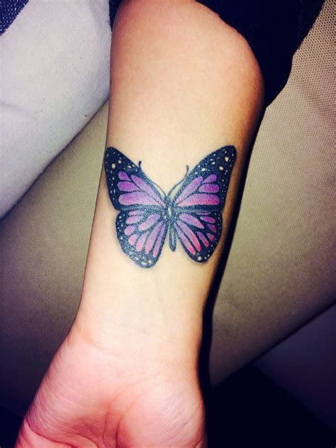 purple and black butterfly tattoo on wrist