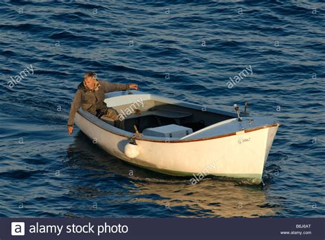 old man on boat old man in small boat fishing with hand line stock photo