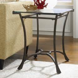 Wrought iron wedge shaped end table with glass top aside tweed sofa