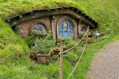 the magic of a hobbit house a hobbit house tucked into the hill overlooking the pond