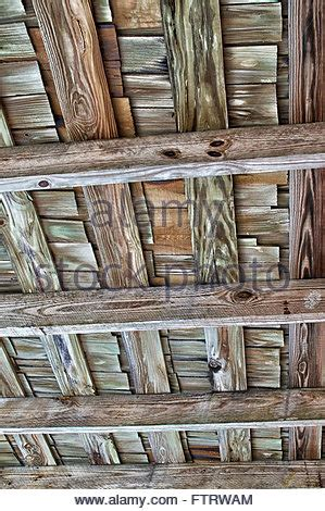 looking up at roof shingles roof shingles and planks of wood on the edge of a garden