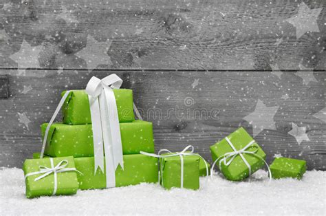 green christmas presents with snow on grey wooden