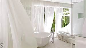 Sheer curtains blowing in breeze in modern white bathroom stock