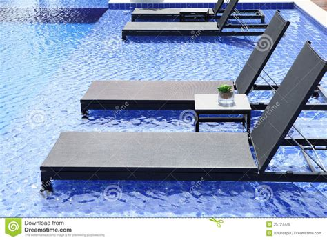 Pool Beds by Swimming Pool And Chairs Bed With Blue Water Stock Image