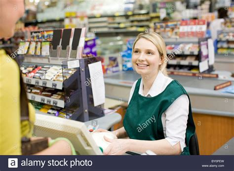 cashier and customer at supermarket checkout stock