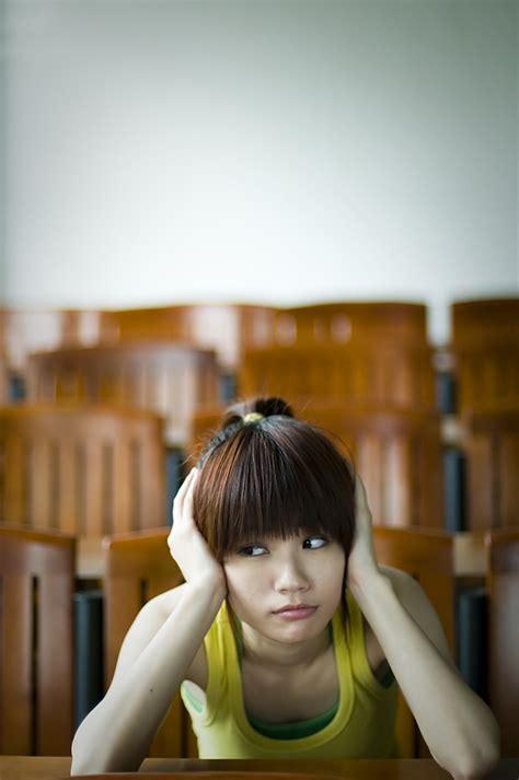 tired girl  stock photo  beautiful chinese girl sitting tired   desk