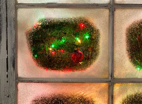 hanging christmas lights in windows easy snowy windows with ornament hanging on fir tree with glowing stock photo image of festive