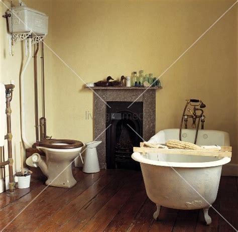 toilette und bd in einem stehende badewanne mit holzablage und toilette in