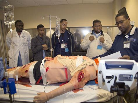 black emergency room far right practitioner monitors the vital signs of a mannequin serving