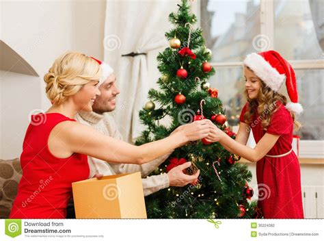 smiling family decorating christmas tree stock photography