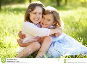 Young Huh two young girls hugging in summer field stock photo