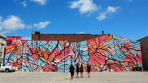 artists repairing defaced downtown muncie mural indiana