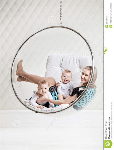 woman swinging baby around young caucasian woman with two babies having fun stock