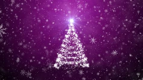 snow falling on a christmas tree tree lights ornaments