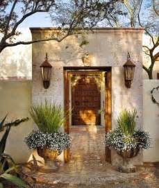 Lovely hacienda style entry with planters and wall sconce lanterns