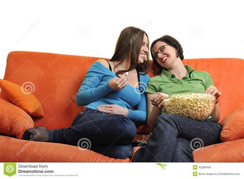 friends orange couch female friends eating popcorn and watching tv at home