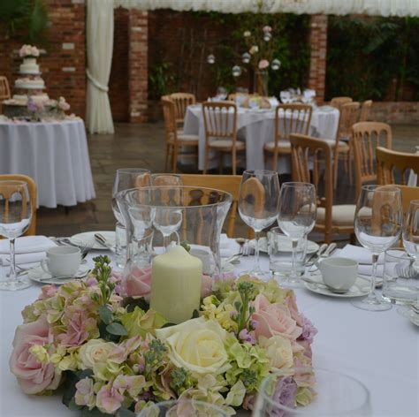 Hurricane lamp table arrangements with candle surrounded
