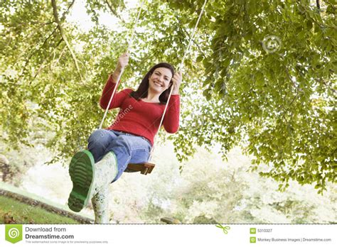 women and swinging young woman on tree swing royalty free stock photography