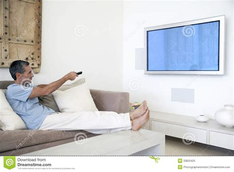 tv in middle of room man using tv remote in living room stock photo image