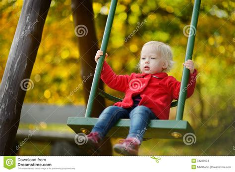is swinging fun adorable girl having fun on a swing stock images image