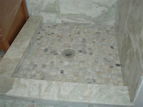 Low marble capped shower curb with higher tile that slopes
