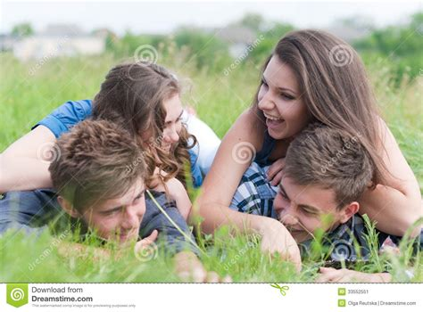 Two Couples Four Friends Lying Together On Green Grass
