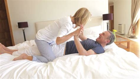 photos of husband and wife in bedroom senior couple having a pillow fight at home in the bedroom