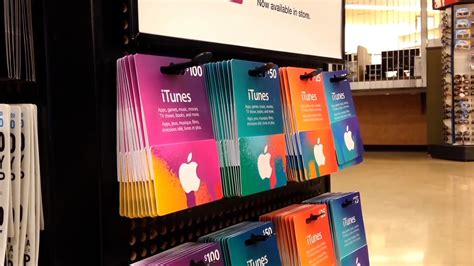 Itunes 20 Dollar Gift Card - man picking fifty and twenty five dollar itunes gift card inside supermarket stock