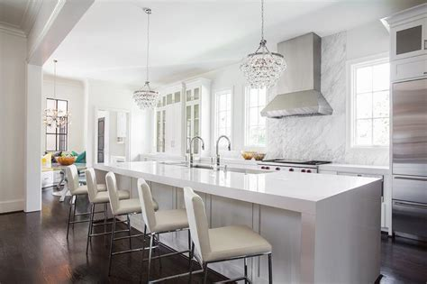 a pair of robert abbey bling chandeliers hang over a white 124 custom luxury kitchen designs part 1