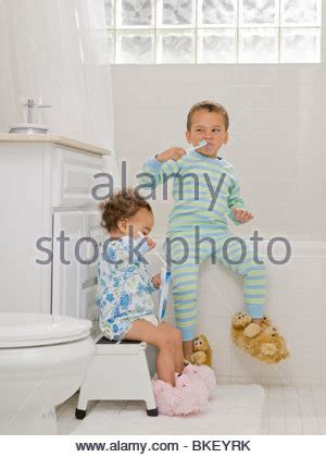 sister brother bathroom boy and girl brushing teeth in bathroom stock photo