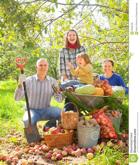Happy Family With Harvest In Garden Stock Photo Image Family Vegetable Garden