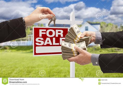 free money for buying a house handing over cash for keys in front of house sign stock