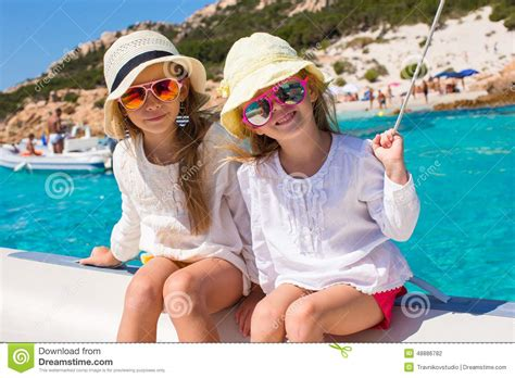 girls on boats little girls sailing on boat in clear open sea stock photo